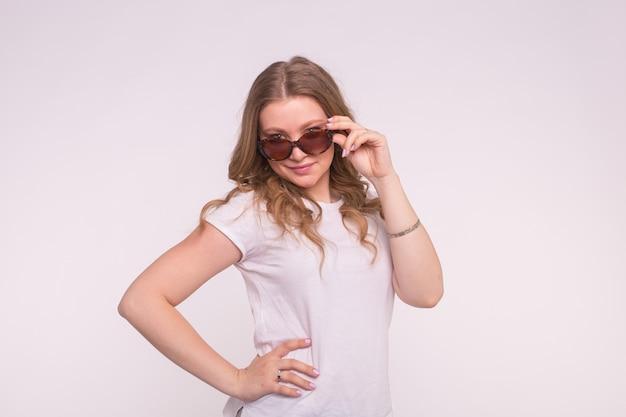 Porträt des rätselhaften schönen weißen mädchens, das das haar repariert, das sonnenbrille auf weiß trägt.