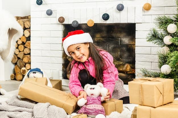 Porträt des recht kleinen mädchens nahe einem kamin im weihnachten
