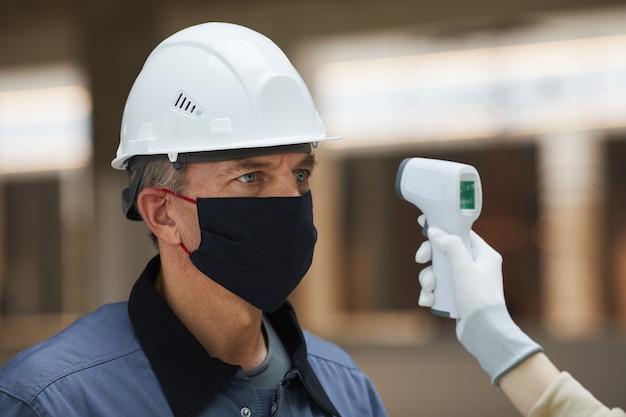 Porträt des reifen arbeiters, der maske trägt und wartet, um temperatur mit kontaktlosem thermometer auf der baustelle zu messen, sicherheit des koronavirus