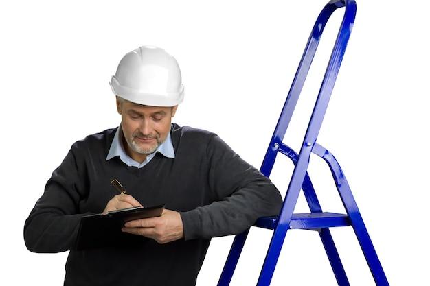 Porträt des reifen bauinspektors. leitender ingenieur, der sich auf leiter stützt und in zwischenablage schreibt