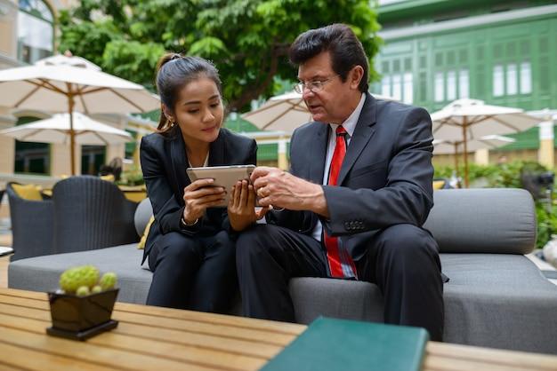 Porträt des reifen geschäftsmannes und der jungen asiatischen geschäftsfrau zusammen als teamvielfaltkonzept im coffeeshop