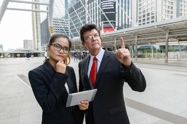 Porträt des reifen geschäftsmannes und der jungen asiatischen geschäftsfrau zusammen als teamvielfaltkonzept in der stadt im freien