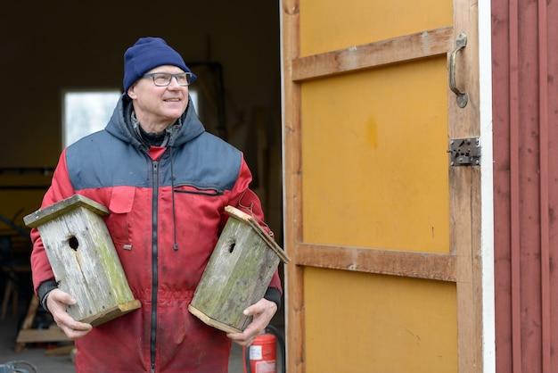 Porträt des reifen gutaussehenden skandinavischen mannes, der vogelhaus drinnen macht