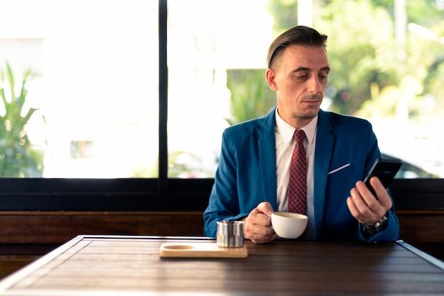 Porträt des reifen hübschen italienischen geschäftsmannes, der am kaffeehaus entspannt
