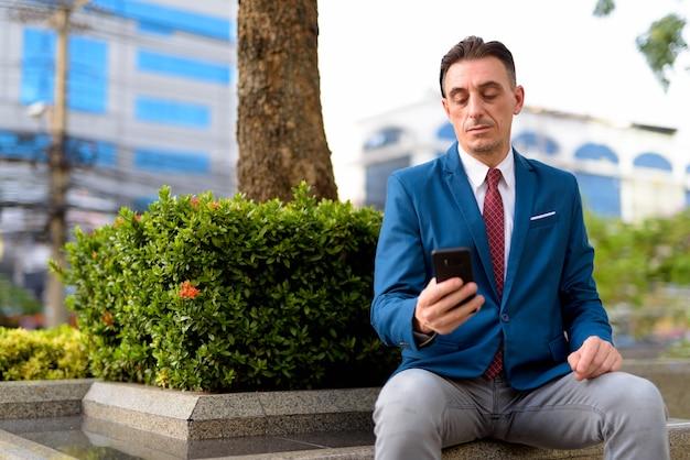 Porträt des reifen hübschen italienischen geschäftsmannes, der außerhalb des gebäudes sich entspannt