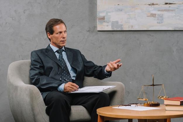 Porträt des reifen männlichen rechtsanwalts, der diskussion im gerichtssaal hat