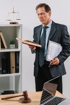 Porträt des reifen männlichen rechtsanwalts, der vertragsdokument und stiftlesebuch hält