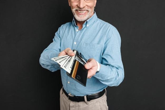 Porträt des reifen mannes 60s mit grauem haar und bart, der brieftasche mit geld hält, das reich und glücklich ist, lokalisiert über schwarzer wand