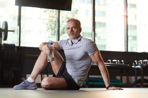 Porträt des reifen mannes, der auf dem boden sitzt und wasser von der flasche trinkt, die er nach sporttraining im fitnessstudio ruht