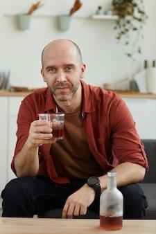 Porträt des reifen mannes, der auf sofa mit glas whisky sitzt. er ruht zu hause