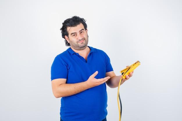 Porträt des reifen mannes, der bauwerkzeuge im blauen t-shirt hält und nachdenkliche vorderansicht schaut