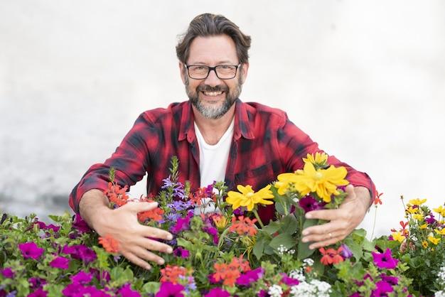 Porträt des reifen mannes, der frische blühende pflanzen hält. lächelnder mann mit verschiedenen blumen. hobbygärtnern. männlicher florist kümmert sich um frisch gewachsene blumen
