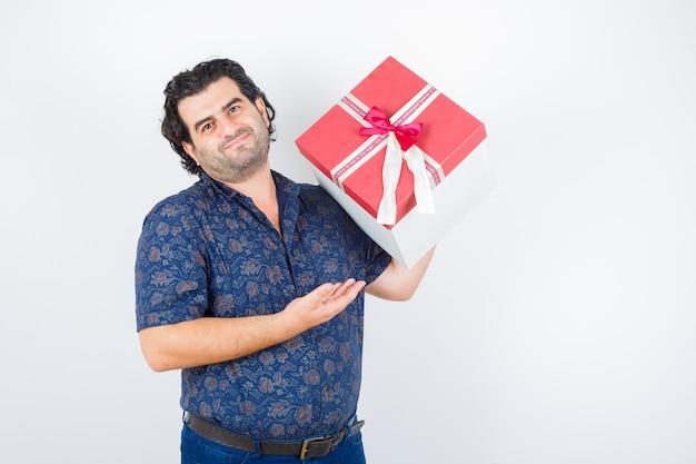 Porträt des reifen mannes, der geschenkbox hält, während im hemd präsentiert und fröhliche vorderansicht schaut