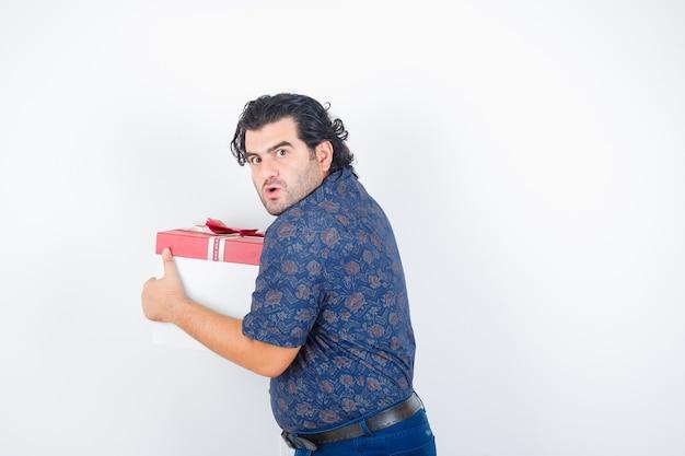 Porträt des reifen mannes, der geschenkbox im hemd hält und verwirrte vorderansicht schaut