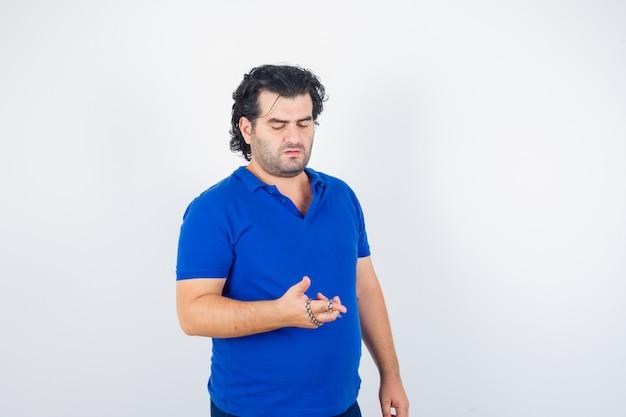 Porträt des reifen mannes, der kette hält, die von hand in blaues t-shirt gewickelt wird und nachdenkliche vorderansicht schaut