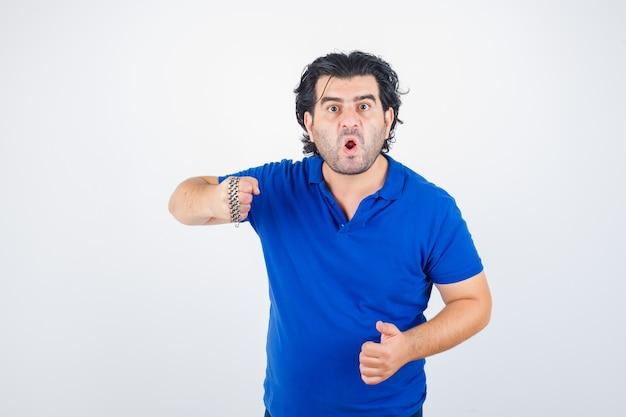 Porträt des reifen mannes, der mit kette droht, die durch faust in blaues t-shirt gewickelt wird und aggressive vorderansicht schaut