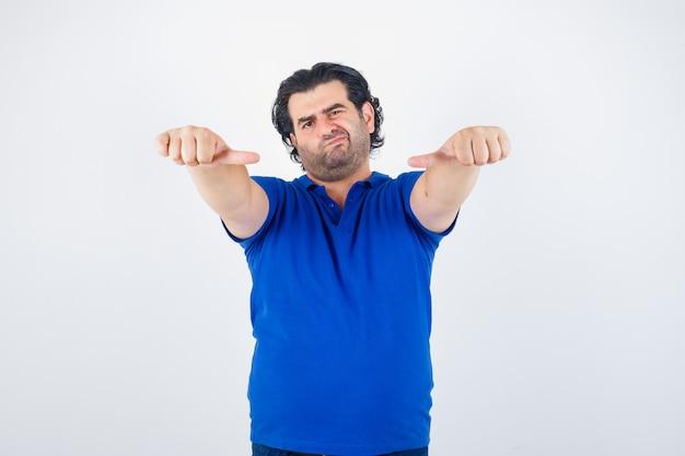 Porträt des reifen mannes, der mittlere daumen im blauen t-shirt zeigt und unentschlossene vorderansicht schaut
