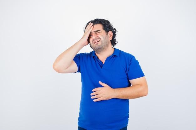 Porträt des reifen mannes, der unter starken kopfschmerzen im blauen t-shirt leidet und genervte vorderansicht schaut
