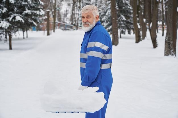 Porträt des reinigers im overall mit schneeschauer.