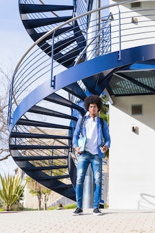 Porträt des reizend hübschen männlichen studenten der universität, der vor blauem wendeltreppe steht