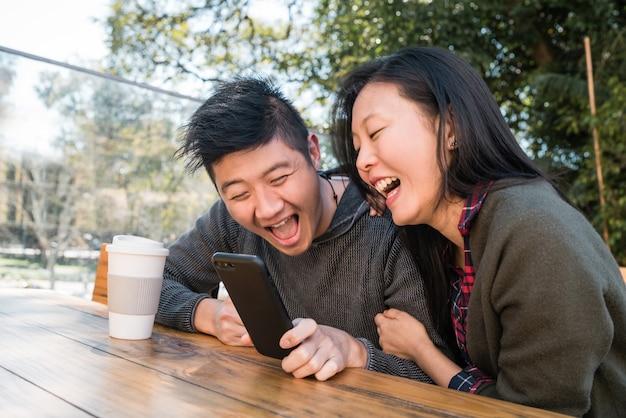 Porträt des reizenden asiatischen paares, das das handy beim sitzen und verweilen im café betrachtet. liebes- und technologiekonzept.