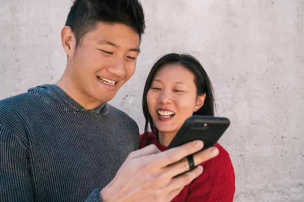Porträt des reizenden asiatischen paares, das das handy betrachtet, während gute zeit zusammen verbringt. liebes- und technologiekonzept.