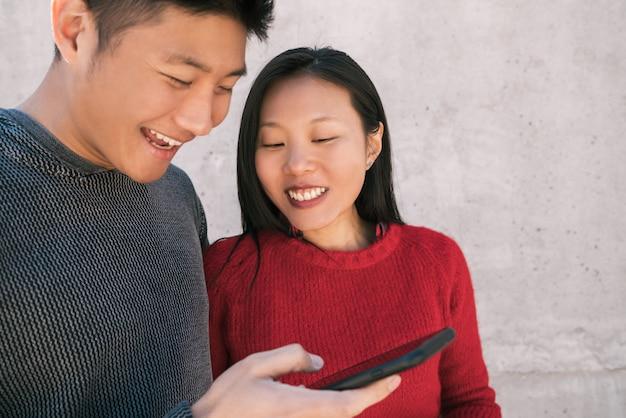 Porträt des reizenden asiatischen paares, das das handy betrachtet, während gute zeit zusammen verbringt.
