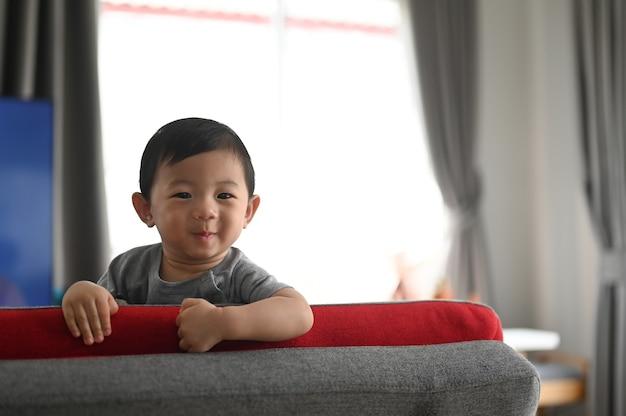 Porträt des reizenden hppy babyjungen, der auf couch in bequemem haus sitzt.