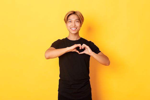 Porträt des reizenden hübschen blonden asiatischen mannes, der herzgeste zeigt und lächelnd, stehende gelbe wand zeigt
