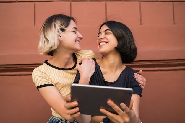 Porträt des reizenden lesbischen paares, das zeit zusammen verbringt und selfie mit digitalem tablett draußen auf der straße nimmt. lgbt-konzept.