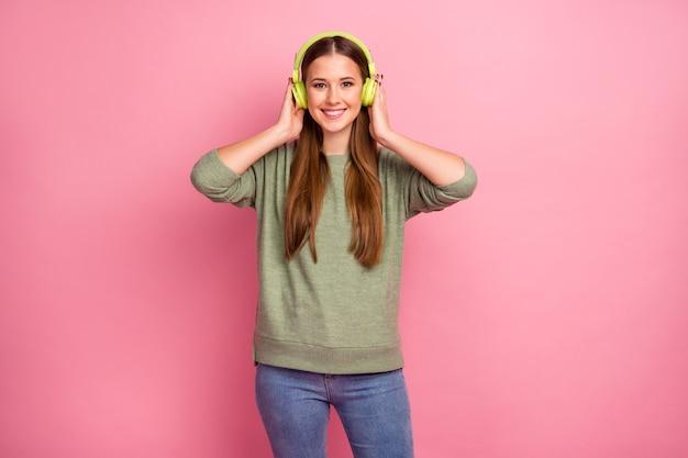 Porträt des reizenden reizenden hübschen mädchens hören musik im headset