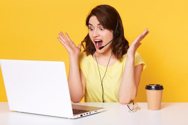 Porträt des reizenden weiblichen betreibers, der am tisch mit laptop auf sitzt. junge brünette frau überrascht mit offenem mund