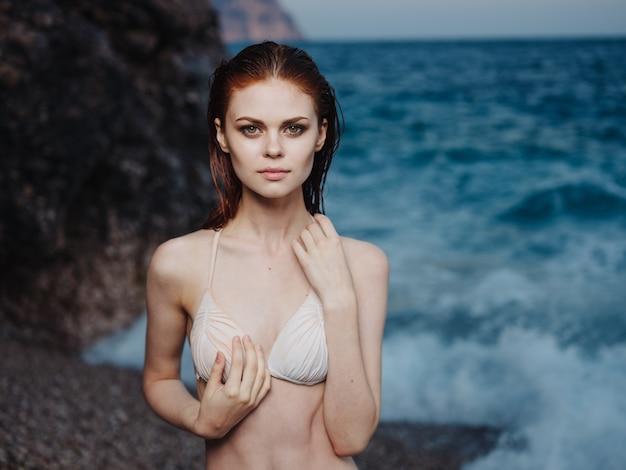 Porträt des reizenden weißen badeanzugmodells der frau und des weißen schaumstrandes des blauen meeres.