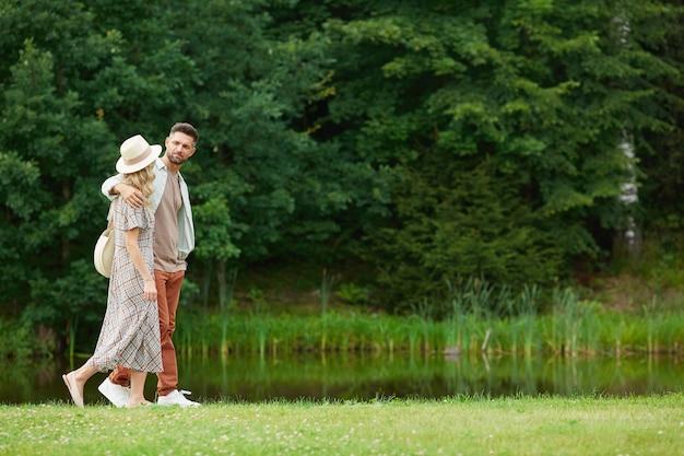 Porträt des romantischen erwachsenen paares, das beim gehen durch fluss in der rustikalen landschaftsumarmung umarmt