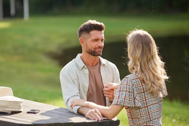 Porträt des romantischen erwachsenen paares, das hände hält und einander mit liebe ansieht, während es am tisch im freien am see sitzt