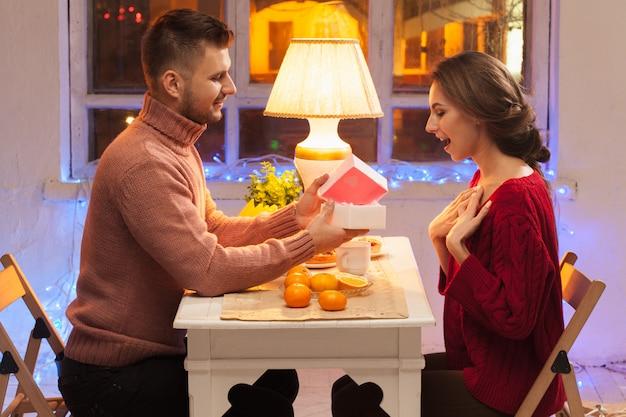 Porträt des romantischen paares am valentinstagessen mit geschenk