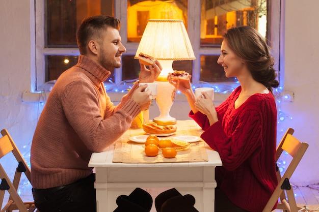 Porträt des romantischen paares am valentinstagessen mit kerzen