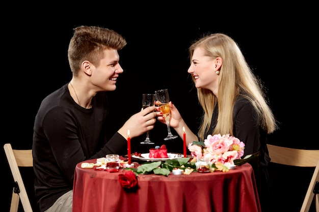 Porträt des romantischen paares, das weißwein beim abendessen röstet