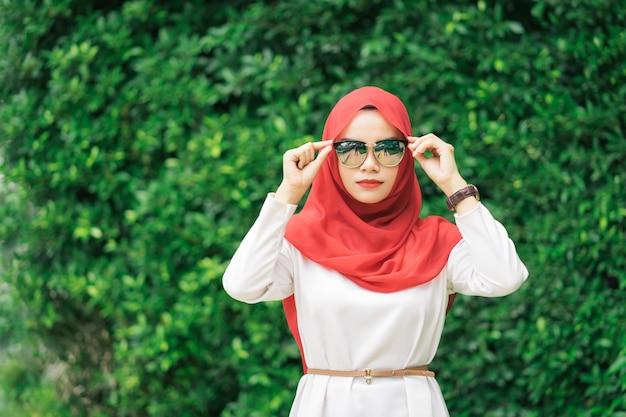 Porträt des roten hijab der glücklichen jungen moslemischen frau verwischte vorbei das grüne feld