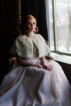Porträt des rothaarigen mädchens, das hochzeitskleid gegen ein weißes studio trägt.