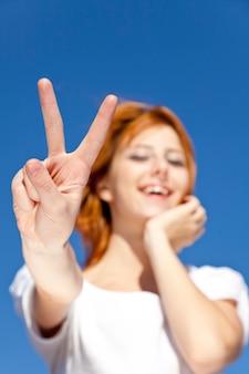 Porträt des rothaarigen mädchens im weiß, das symbol der hand v zeigen.