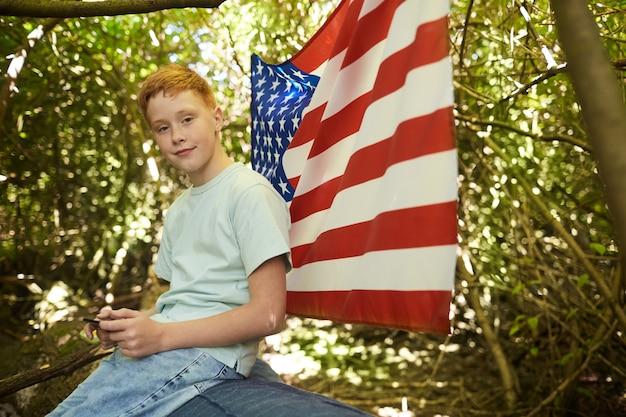 Porträt des rothaarigen teenagers im freien, während unter zweigen des großen baumes im wald versteckt oder im hinterhof mit amerikanischer flagge spielend