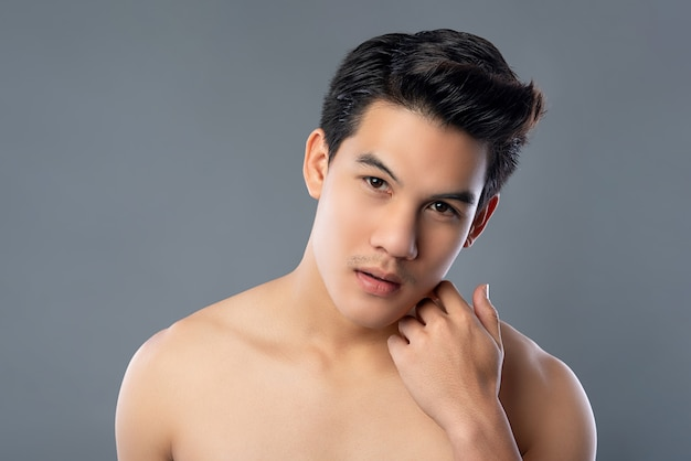 Porträt des rührenden gesichtes des hemdlosen jungen asiatischen gutaussehenden mannes