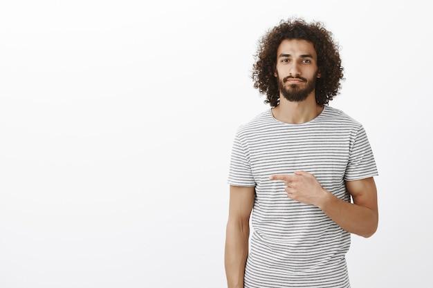 Porträt des ruhigen attraktiven östlichen männlichen modells mit lockiger frisur im trendigen t-shirt, nach links zeigend und mit lässigem ausdruck lächelnd