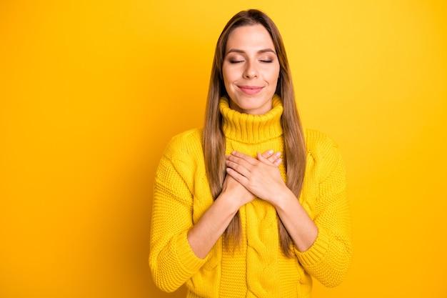 Porträt des ruhigen friedlichen positiven mädchens fühlen sich dankbar verträumt hände auf der brust tragen warmen weichen pullover isoliert über helle farbe wand