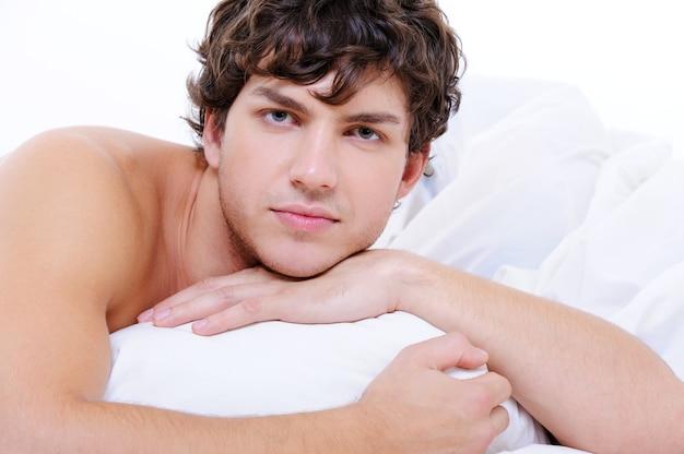Porträt des ruhigen mannes mit einem schönen gesicht, das im bett mit kissen liegt