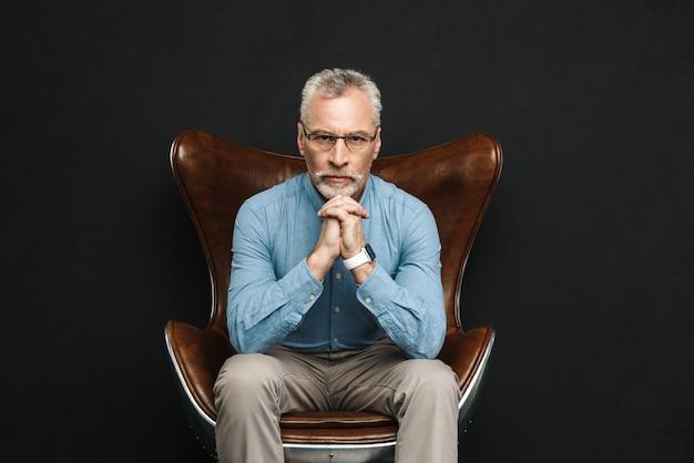 Porträt des sachlichen herrn der 50er jahre mit grauem haar und bart in gläsern, die auf holzsessel mit strengem blick sitzen, lokalisiert über schwarzer wand