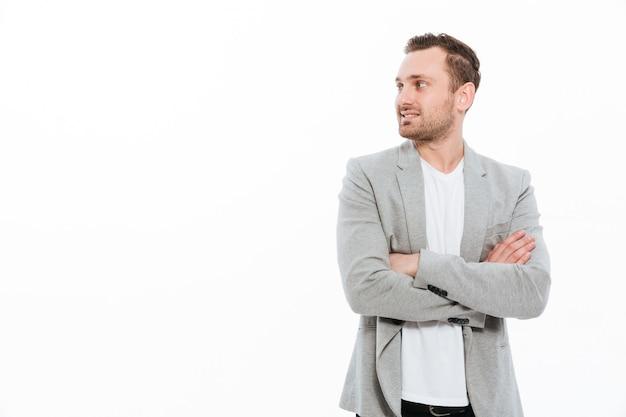 Porträt des sachlichen mannes in der jacke, die mit dem breiten lächeln hält arme gefaltet und beiseite schaut, lokalisiert über weißem wandkopienraum aufwirft