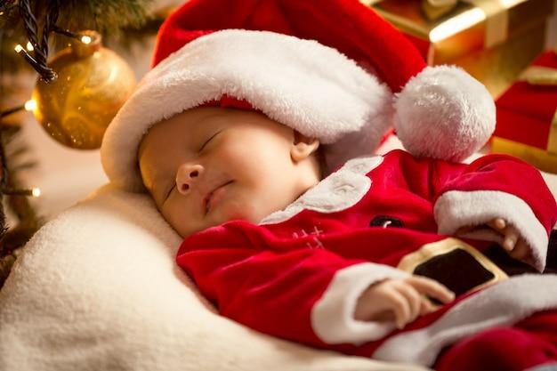 Porträt des säuglingsbabys im sankt-kostüm, das unter weihnachtsbaum liegt. weihnachtskonzept