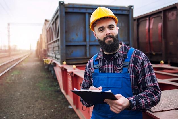 Porträt des schifffahrtsarbeiters, der zwischenablage hält und frachtcontainer über eisenbahn versendet